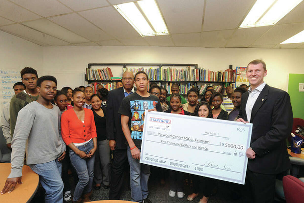 Photo by Matthew Vinci Chris Meek, right chairman of the nonprofit START Now! and candidate for the state's Fourth District seat in the U.S. Congress, presents a check to the Yerwood Center in Stamford on Monday. Holding the check is student Steve Pierre-Louis and on his left is Yerwood Center President and CEO Eugene Campbell CEO , along with other Stamford students.