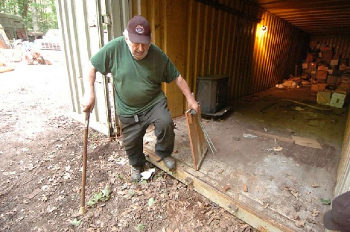 Photo by Alex von Kleydorff. Ted Coley grabs some items from a storage trailer like the drawing table he made in High School.