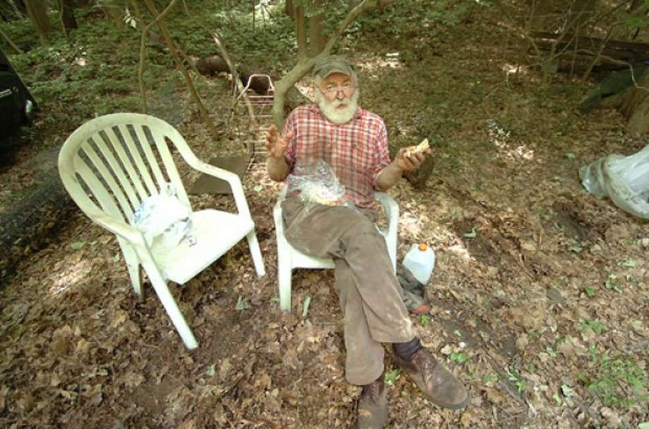 Photo by Alex von Kleydorff. Fred Coley takes a moment to have lunch while helping his brother Ted clear storage trailer on his Weston property.