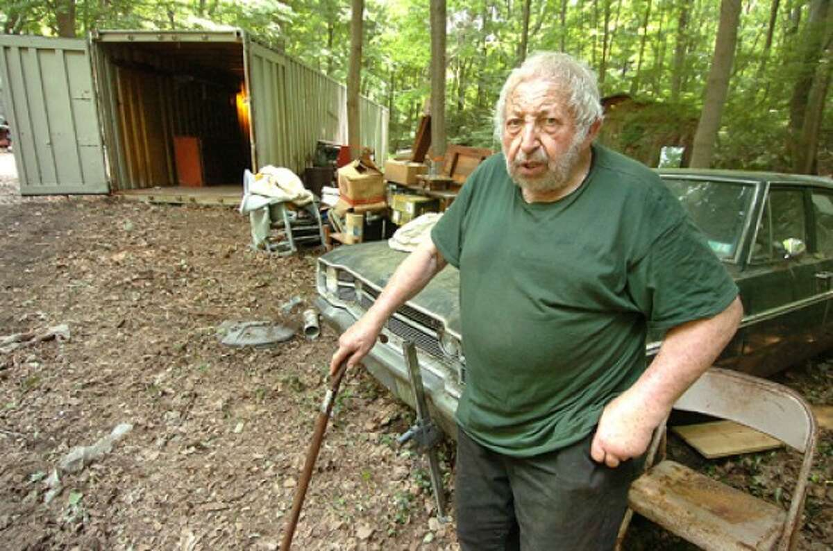 Photo by Alex von Kleydorff. Ted Coley makes his way through his back yard while clearing items from storage trailers.