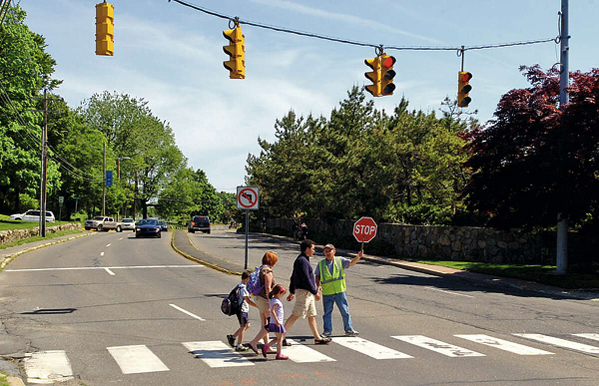 A family crosses Calf Pasture Beach Rd. after leaving Marvin Elementary School Friday. Common Council's Public Works Committee to hold special meeting May 31 on safety on Calf Pasture Beach Road. Hour photo / Erik Trautmann