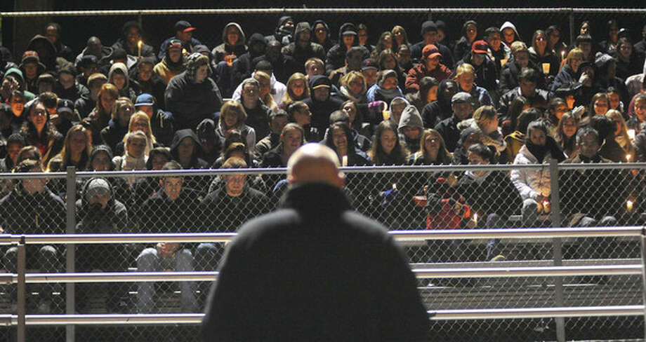 Hour photo / John Nash More than 800 mourners showed up at Casagrande Field at Brien McMahon High School Friday evening for a candlelight vigil in the memory of former Senators standout athlete James Shaw. The Rev. John Livingston of United Church of Rowayton, bottom center, addressed the crowd.