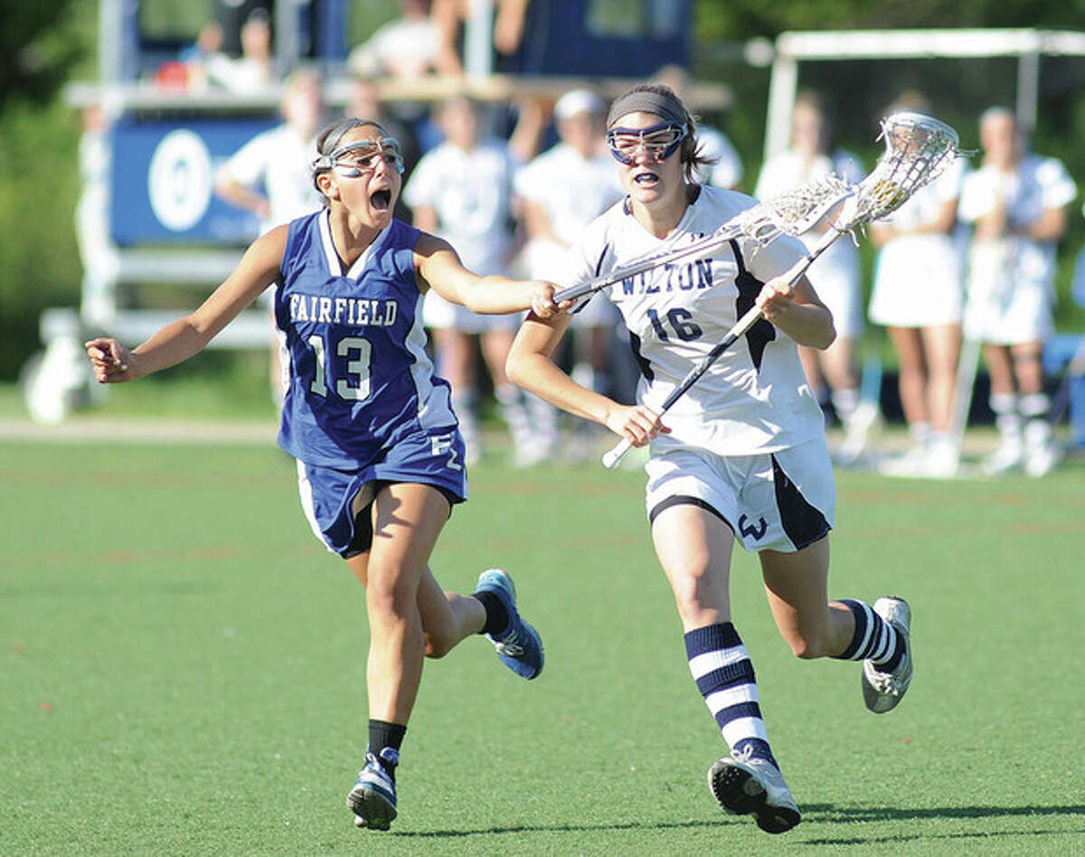 Hour photo/John Nash Wilton's Tegan Helms, right, races along side Fairfield Ludlowe defender Steph Gorab during the second half of Friday's FCIAC girls lacrosse quarterfinal at Lilly Field. The third-seeded Warriors defeated Ludlowe, 13-7, to advance to a semifinal match against No. 2 Greenwich.