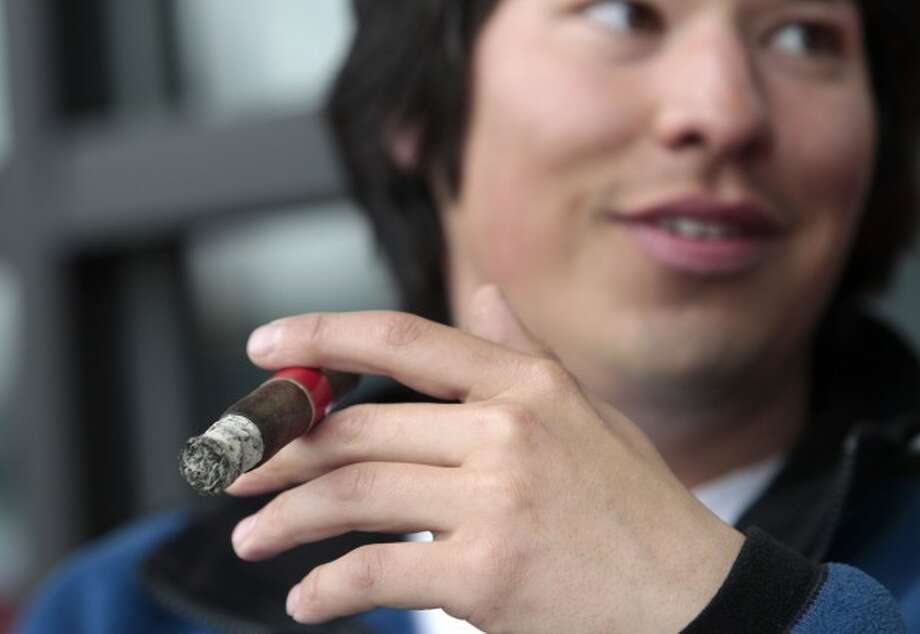 This Thursday, April 14, 2011 photo shows Jameson Florence as he smokes a La Traviata cigar outside the Rain City Cigar shop in Seattle. Washington used to have cigar bars and lounges. But a ban on all indoor smoking in 2005 put them out of business. A bill introduced in the Legislature this year that would allow a limited number of cigar lounges and bars has languished in committee, after getting vehement opposition from the state Department of Health. (AP Photo/Elaine Thompson)