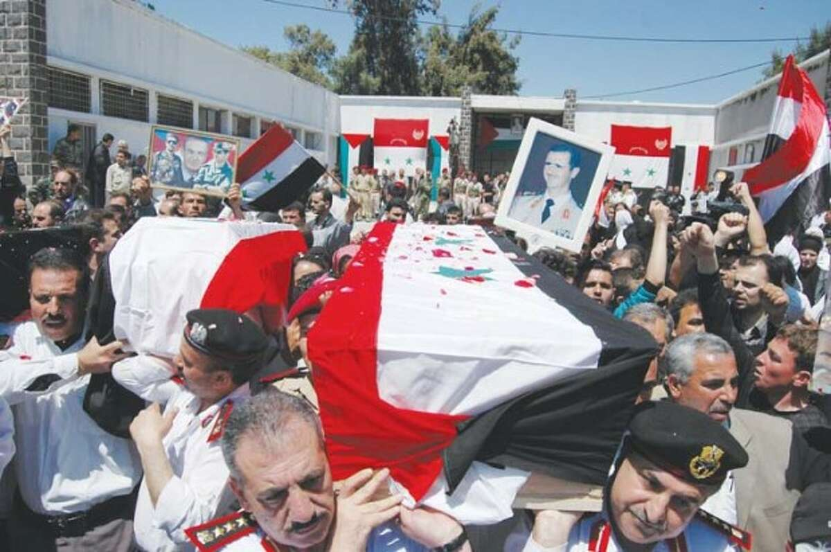 In this photo released by the Syrian official news agency SANA, Syrian military police carry coffins as they prepare to send the bodies of eleven killed soldiers and security force members to their families for burial, out of a military hospital in the central city of Homs, Syria, Saturday, May 7, 2011. The agency did not report the circumstances of their deaths but they are believed to have been victims of the ongoing civil unrest against the government. (AP Photo/SANA) EDITORIAL USE ONLY