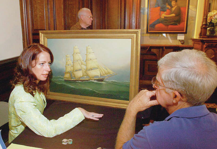 Hour photo / Erik Trautmann Christine Downing of Downing Auctions looks over a painting brought in to the second annual Antiques Appraisals Weekend at Lockwood Mathews Mansion Museum by James Buchta in this file photo.