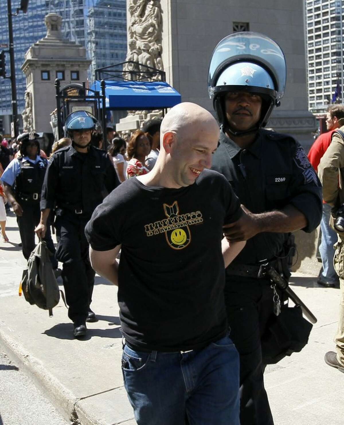 Steve Salsman, 38, from Galesburg, Ill., is taken into custody by a Chicago Police officer during a demonstration Friday, May 18 2012, in Chicago. Thousands of nurses and other protesters gathered for the noisy but largely peaceful demonstration with a broad spectrum of causes, from anti-war activists to Occupy protesters to a Chicago Women's AIDS project. The demonstrations Friday were the largest yet ahead of a two-day NATO summit that is expected to draw even larger protests. (AP Photo/Charles Rex Arbogast)
