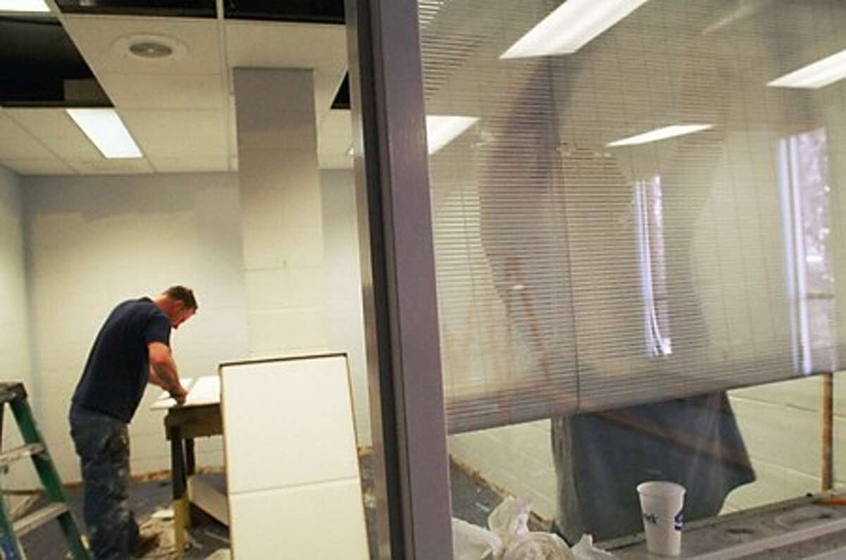 Adam Zavrozny and Vincent Mauro of Concrete Creations install a ceiling and paint in the second floor offices as part of the ongoing renovations at the Health Department building on East Ave. Hour photo / Erik Trautmann