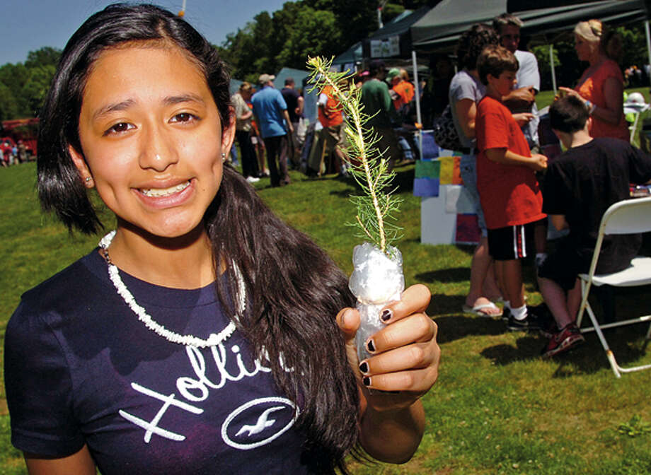 Lelsie Rivas got a evergreen sapling at the Norwalk-Wilton Tree Festival Saturday in Cranbury Park. Hour photo / Erik Trautmann / (C)2012, The Hour Newspapers, all rights reserved