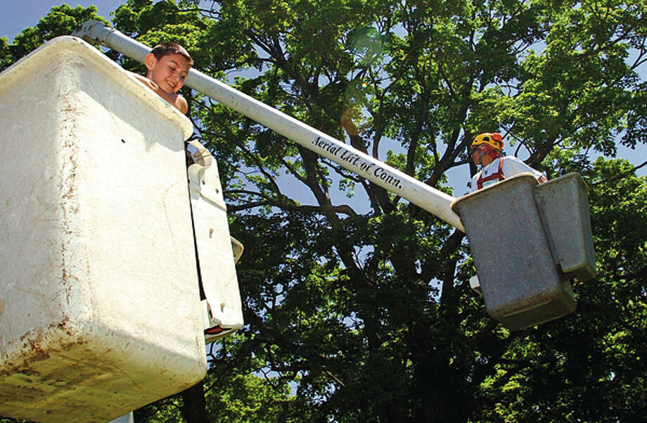 11 year old Peter Baez gets brought up in a bucket lift at the Norwalk-Wilton Tree Festival Saturday in Cranbury Park. Hour photo / Erik Trautmann / (C)2012, The Hour Newspapers, all rights reserved