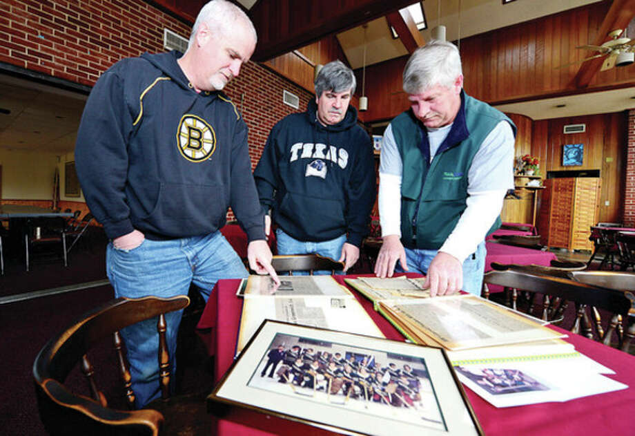 Hour photo / Erik TrautmannThe Welch Brothers, from left, Steve, better known as Zip, Rick and Kevin were probably the best hockey family to come out of Norwalk. Here, the three look over scrapbooks from their playing days. / (C)2013, The Hour Newspapers, all rights reserved