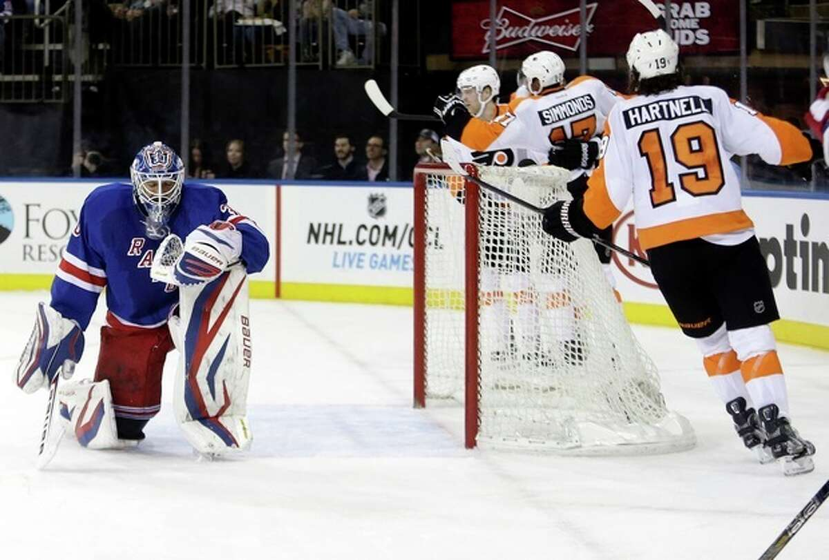 New York Rangers goalie Henrik Lundqvist, left, of Sweden, reacts as Philadelphia Flyers' Jakub Voracek, obscured, celebrates a goal with Wayne Simmonds, second from right, and Scott Hartnell, right, during the first period of an NHL hockey game Tuesday, March 5, 2013, in New York. (AP Photo/Frank Franklin II)