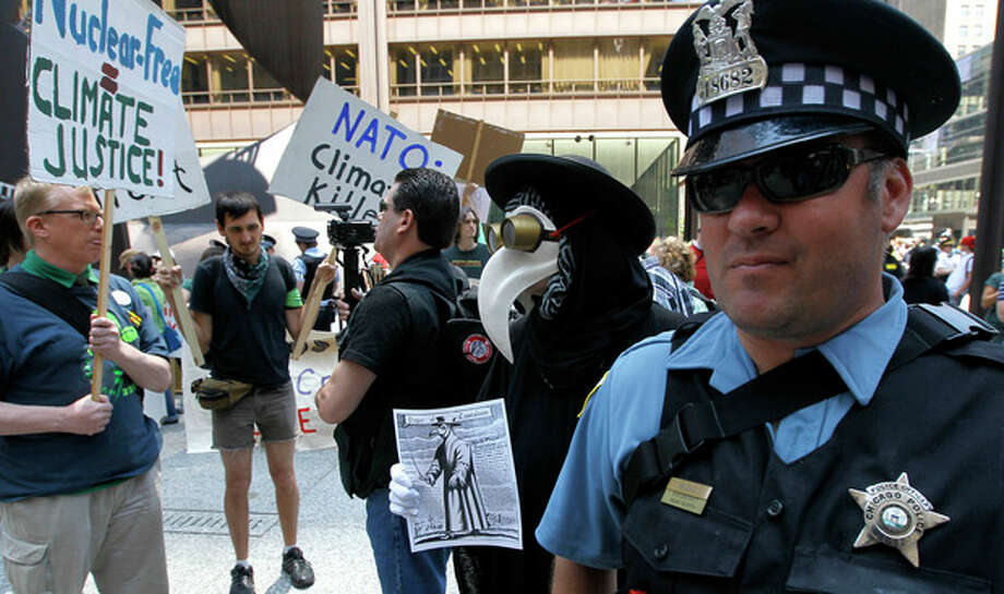 Protesters gather in Daley Plaza near Chicago police officer Ruzas during a demonstration in advance of this weekend's NATO summit, Friday, May 18 2012, in Chicago. (AP Photo/Charles Rex Arbogast) / AP