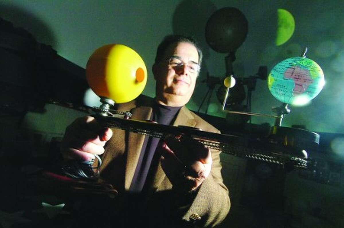Photo/Alex von Kleydorff. Ralph Mackenstein holds an Orrery in the Planetarium at Roton Middle school