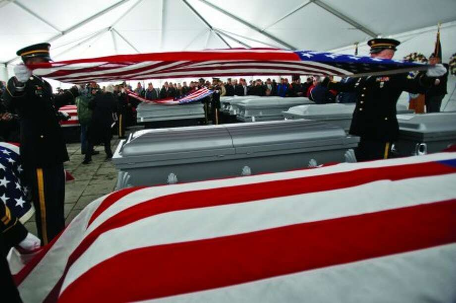 Members of a military honor guard fold the American flag that draped one of the 20 U.S. military veterans'' caskets whose remains were unclaimed during their burial ceremony at Calverton National Cemetery, Saturday, Jan. 8, 2011, in Calverton, N.Y. The ceremony, sponsored by the Dignity Memorial network, has provided services for more than 850 veterans since its inception in 2000. (AP Photo/Mary Altaffer)
