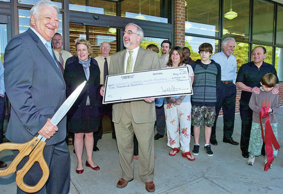 Norwalk mayor Richard Moccia is surprised by a $5000 donation to the City Youth Employment Program from Wine Nation CEO Thomas Trone during the ribbon cutting ceremony for their new store on Main Ave Friday.Hour photo / Erik Trautmann / (C)2012, The Hour Newspapers, all rights reserved