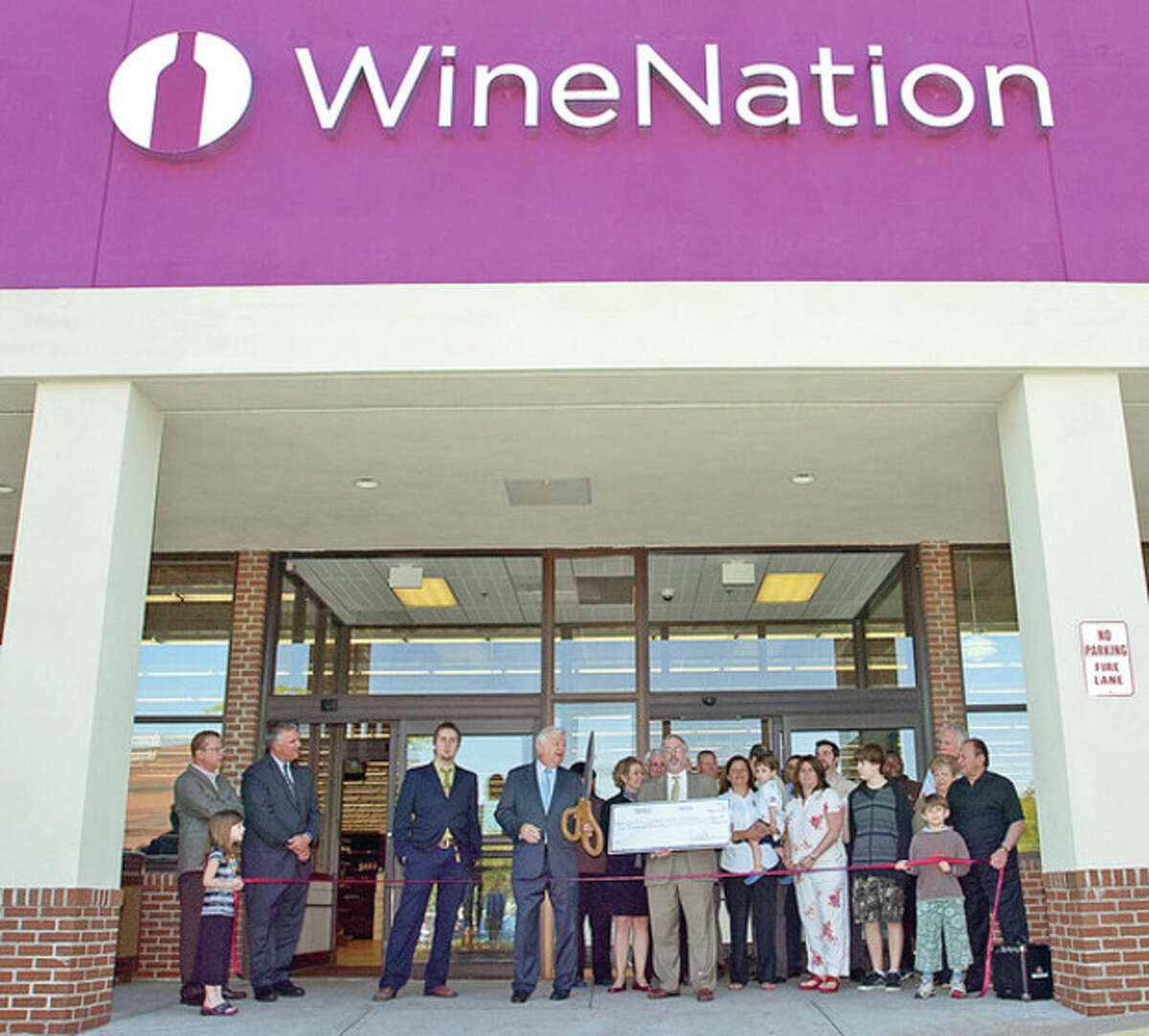 Norwalk mayor Richard Moccia, Wine Nation CEO Thomas Trone, friends and family gather outside the store during the ribbon cutting ceremony for their new store on Main Ave Friday. Hour photo / Erik Trautmann