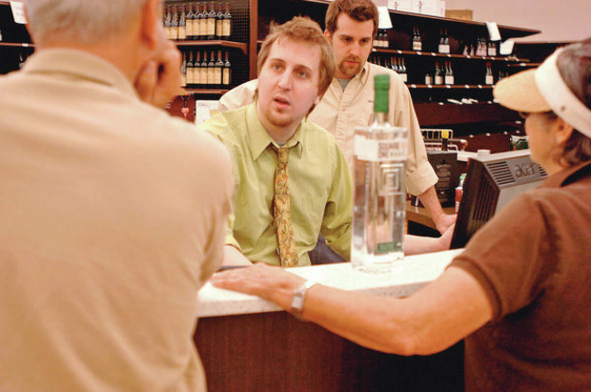Taylor Trone and Andrew Meisner help customers at Wine Nation on Main Ave in Norwalk. Hour photo / Erik Trautmann
