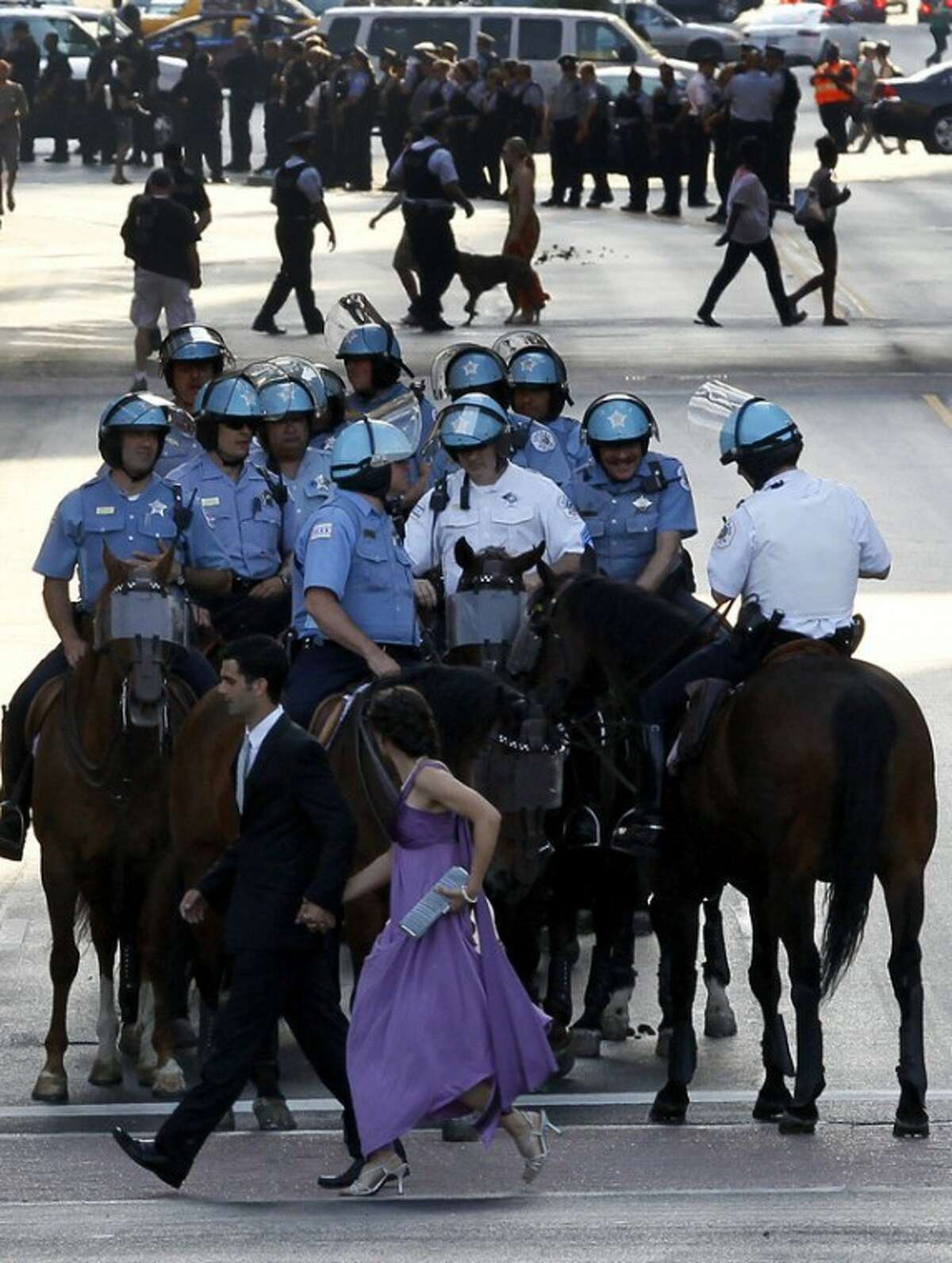 A couple dressed hustle past the Chicago police department's mounted patrol, as members of Occupy Chicago march through the street Saturday, May 19 2012, in Chicago. Security has been high throughout the city in preparation for the NATO summit, where delegations from about 60 countries will discuss the war in Afghanistan and European missile defense. (AP Photo/Charles Rex Arbogast)