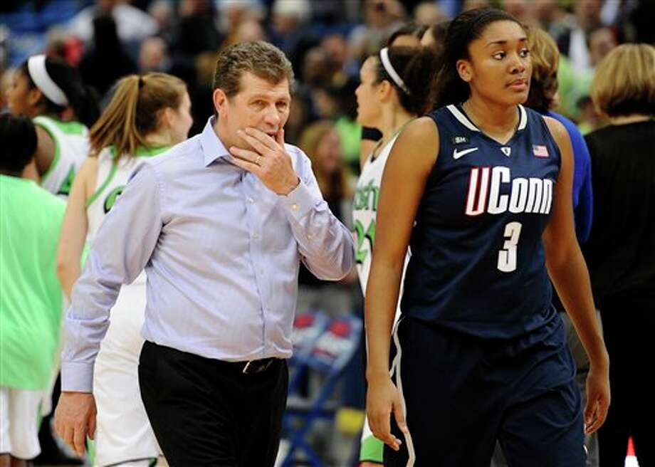 Connecticut head coach Geno Auriemma left, walks off the court with Connecticut's Morgan Tuck after their 61-59 loss to Notre Dame in an NCAA college basketball game in the final of the Big East Conference women's tournament in Hartford, Conn., Tuesday, March 12, 2013. (AP Photo/Jessica Hill) / FR125654 AP