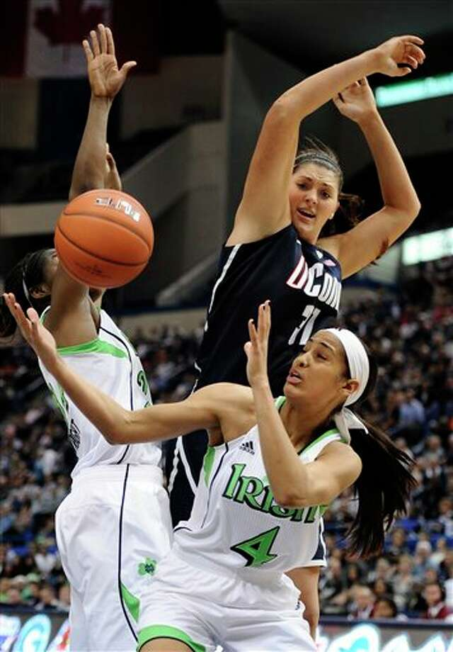 Connecticut's Stefanie Dolson top battle for a rebound with Notre Dame's Skylar Diggins, bottom, and Notre Dame's Markisha Wright, left, in the second half of an NCAA college basketball game in the final of the Big East Conference women's tournament in Hartford, Conn., Tuesday, March 12, 2013. (AP Photo/Jessica Hill) / FR125654 AP