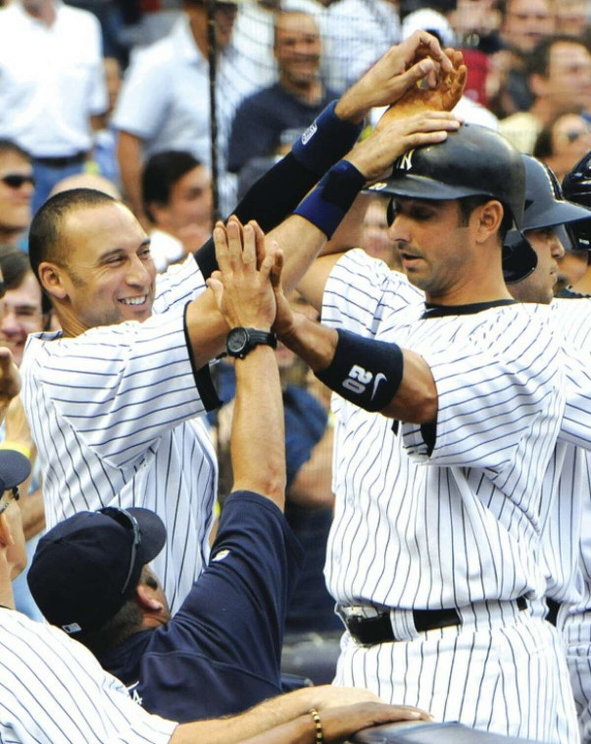 @White=[C] AP photo Jorge Posada, right, high-fives with Derek Jeter and hitting coach Kevin Long, bottom left, after hitting a grand slam during the fifth inning of Saturday's 9-2 win by the Yankees over the Tampa Bay Rays.