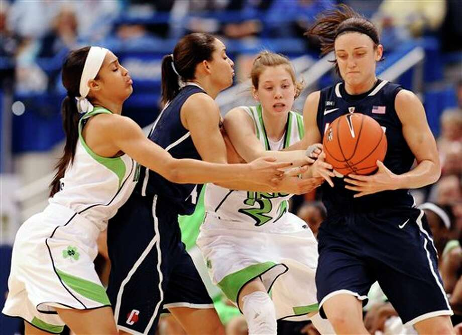 Connecticut's Bria Hartley, second from left, is pressured by Notre Dame's Skylar Diggins, left, and Notre Dame's Madison Cable, second from right, as she passes the ball to Connecticut's Kelly Faris, right, in the first half of an NCAA college basketball game in the final of the Big East Conference women's tournament in Hartford, Conn., Tuesday, March 12, 2013. (AP Photo/Jessica Hill) / FR125654 AP