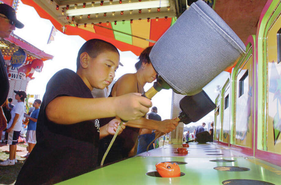Michael Swiander looks to Wack-A-Mole at the 2011 Norwalk Seaport Association Oyster Festival Saturday at Veteran's Memorial Park. / (C)2011, The Hour Newspapers, all rights reserved