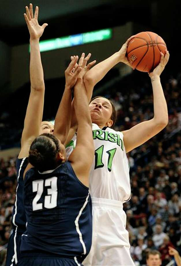 Notre Dame's Natalie Achonwa (11) goes up to the basket while guarded by Connecticut's Kaleena Mosqueda-Lewis (23) and Connecticut's Kiah Stokes, back, first half of an NCAA college basketball game in the final of the Big East Conference women's tournament in Hartford, Conn., Tuesday, March 12, 2013. (AP Photo/Jessica Hill) / FR125654 AP