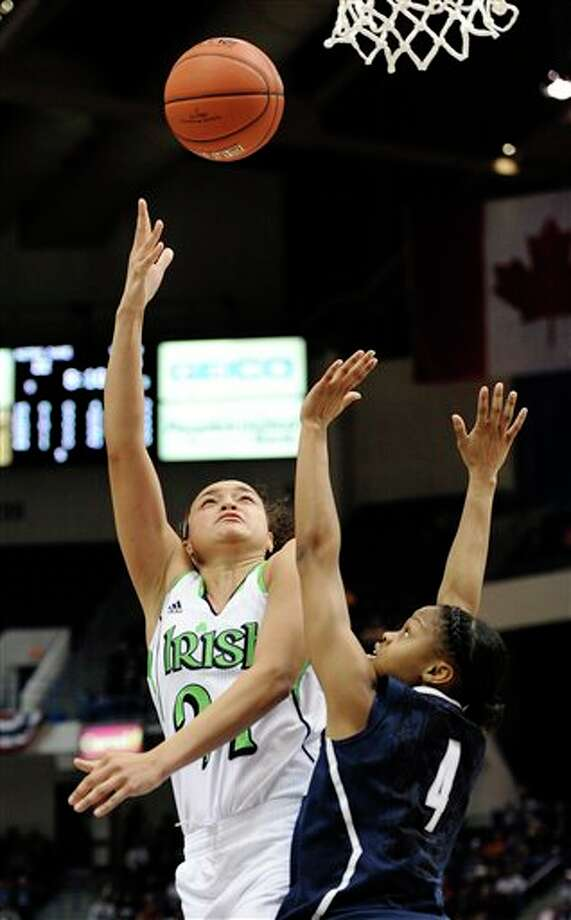 Notre Dame's Kayla McBride goes up for a basket while guarded by Connecticut's Moriah Jefferson in the first half of an NCAA college basketball game in the final of the Big East Conference women's tournament in Hartford, Conn., Tuesday, March 12, 2013. (AP Photo/Jessica Hill) / A2013