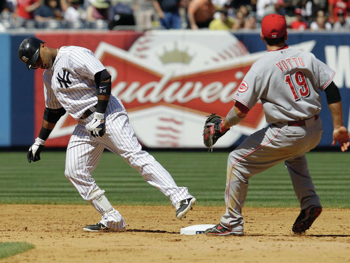AP photo New York Yankees Robinson Cano touches second base with his foot after running past the base on a double as Cincinnati Reds first baseman Joey Votto (19) closes in during Sunday's game at Yankee Stadium in New York. The Reds took the rubber game of the series 5-2.