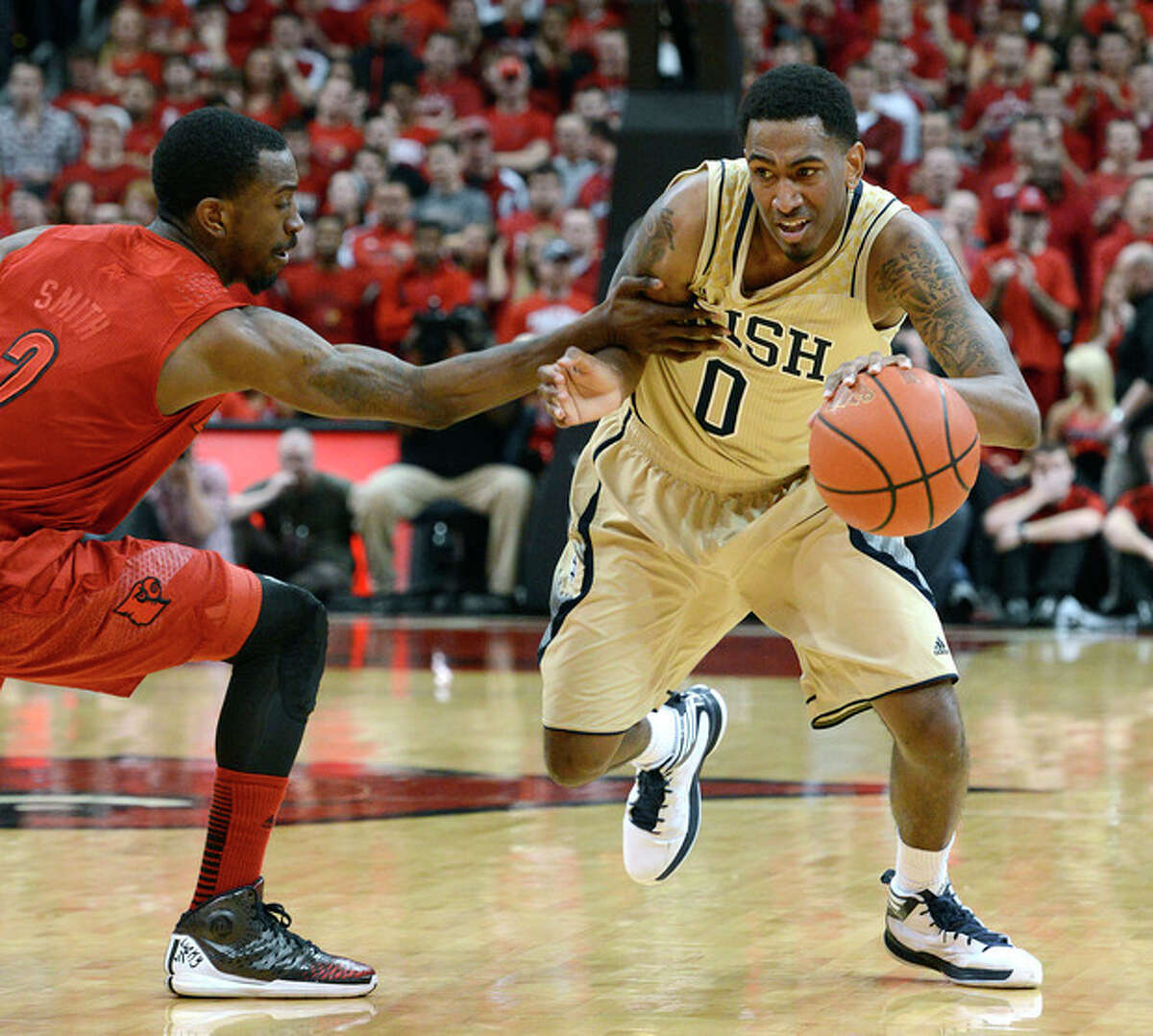 Notre Dame's Eric Atkins, right, drives around the defense of Louisville's Russ Smith during the first half of an NCAA college basketball game on Saturday, March 9, 2013, in Louisville, Ky. Louisville defeated Notre Dame 73-57. (AP Photo/Timothy D. Easley)