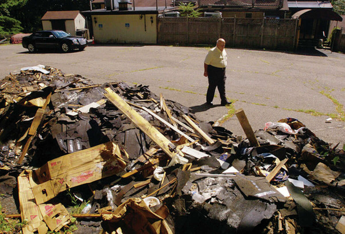 Hour photo / Erik Trautmann Fred Bondi, president of the Building Committee for Sons of Italy on New Canaan Avenue, examines a pile of construction refuse that was dumped onto the back lot of the club.
