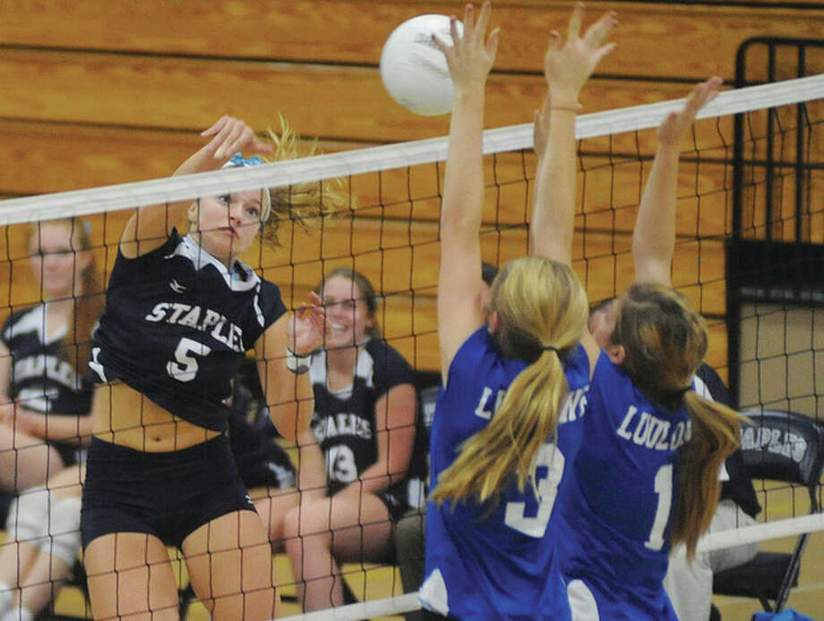 Hour photo/John Nash Staples outside hitter Anna Link spikes the ball toward two members of the Fairfield Ludlowe defense during Monday's game in Westport. Staples won, 3-0.