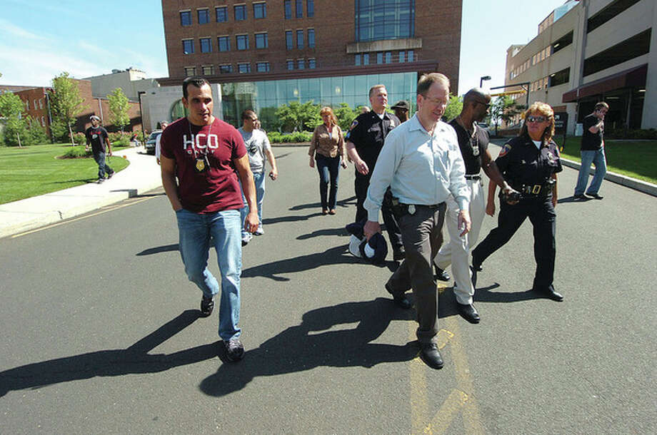 Hour Photo/ Alex von Kleydorff. Stamford Police Sgt. Joe Kennedy is joined by members of the police deparment as they leave the arraignment of Frank Douglas at Stamford Superior Courthouse. / 2012 The Hour Newspapers