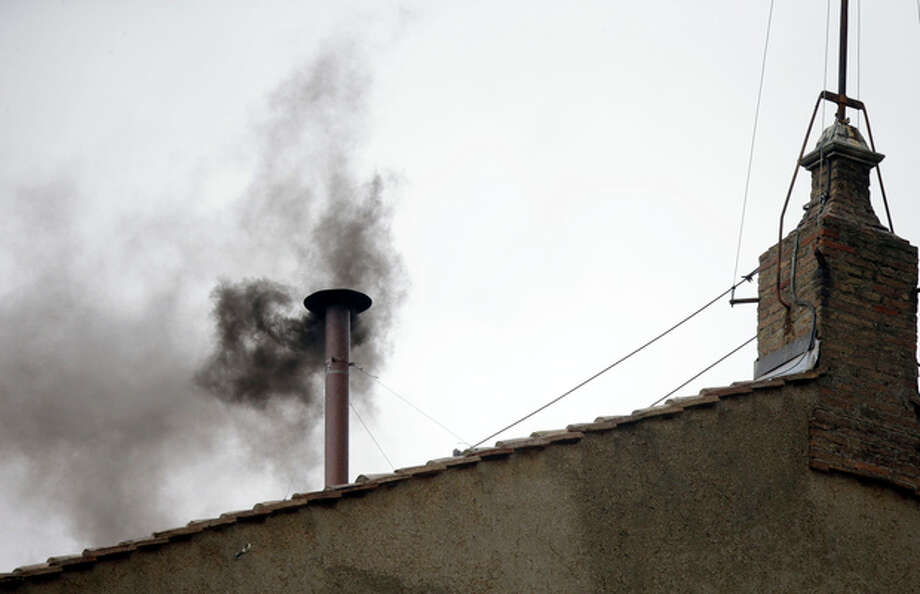 Black smoke emerges from the chimney on the roof of the Sistine Chapel, in St. Peter's Square at the Vatican, Wednesday, March 13, 2013. The black smoke indicates that the new pope has not been elected yet. (AP Photo/Gregorio Borgia) / AP