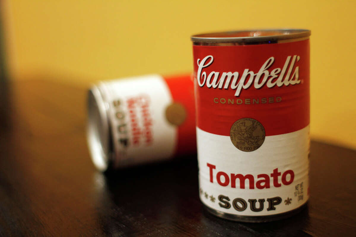 This Aug. 31, 2011 photo shows two cans of Campbell's soup in New York. Campbell Soup Co.'s net income slipped by 5 percent in the latest quarter as it struggled to balance higher costs for ingredients and sluggish soups sales, the company said Monday May 21, 2012. The Camden, N.J.-based company, which is known for its red and white soup cans, is trying to regain lost ground after years of declining soup sales. The efforts include plans to roll out pricier, higher-quality soups and more snacks and beverages. (AP Photo/James H. Collins)