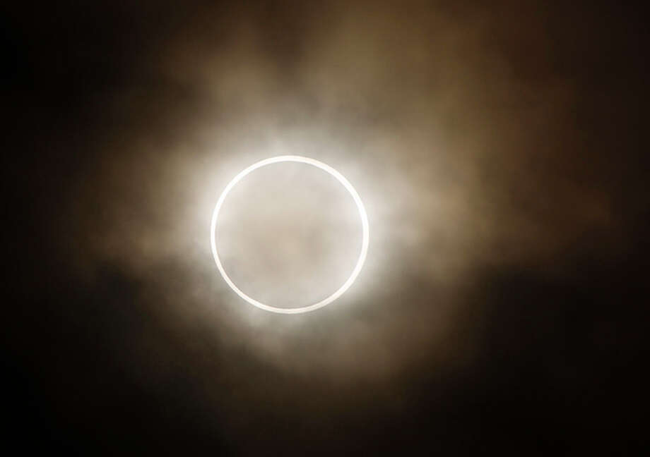 "The moon slides across the sun, showing a blazing halo of light, during an annular eclipse at a waterfront park in Yokohama, near Tokyo, Monday, May 21, 2012. Millions of Asians watched as a rare ""ring of fire"" eclipse crossed their skies early Monday. The annular eclipse, in which the moon passes in front of the sun leaving only a golden ring around its edges, was visible to wide areas across the continent. (AP Photo/Shuji Kajiyama) / AP"