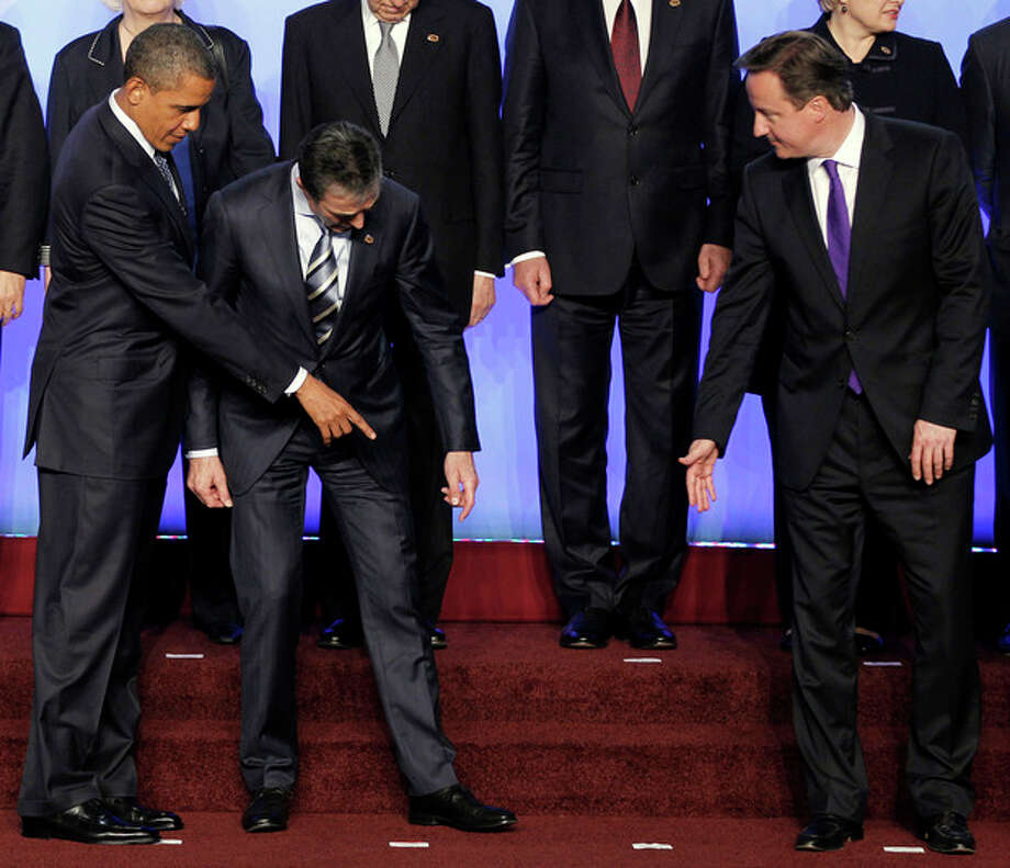 President Barack Obama, left, and British Prime Minister David Cameron, right, help Secretary General Anders Fogh Rasmussen, center, find his toe marker during the NATO family photo at the NATO Summit in Chicago, Sunday, May 20, 2012. (AP Photo/Pablo Martinez Monsivais) / Copyright 2012 The Associated Press. All rights reserved. This material may not be published, broadcast, rewritten or redistributed.