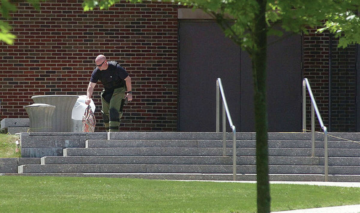 Hour Photo/ Alex von Kleydorff. Stamford Bomb Squad removes a bag from a trash bin outside the Courthouse.