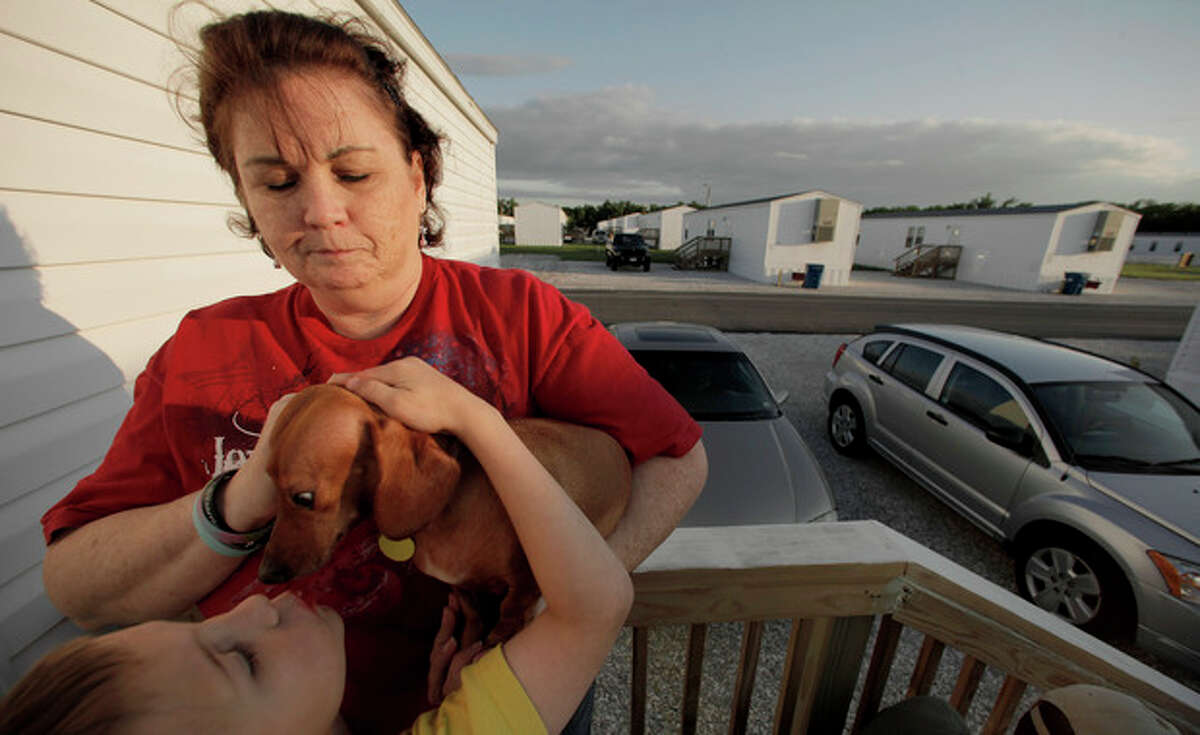 In this photo taken Monday, May 7, 2012, Suzanne Falkner stands with her dog Ginger and her grandson Hunter Johnson, 7, outside the FEMA trailer she shares with her son, daughter-in-law and three grandchildren in Webb City, Mo. Displaced by an EF-5 tornado that tore through the community nearly a year ago, the family was among 600 tornado victims housed by FEMA across 15 sites around Joplin. (AP Photo/Charlie Riedel)