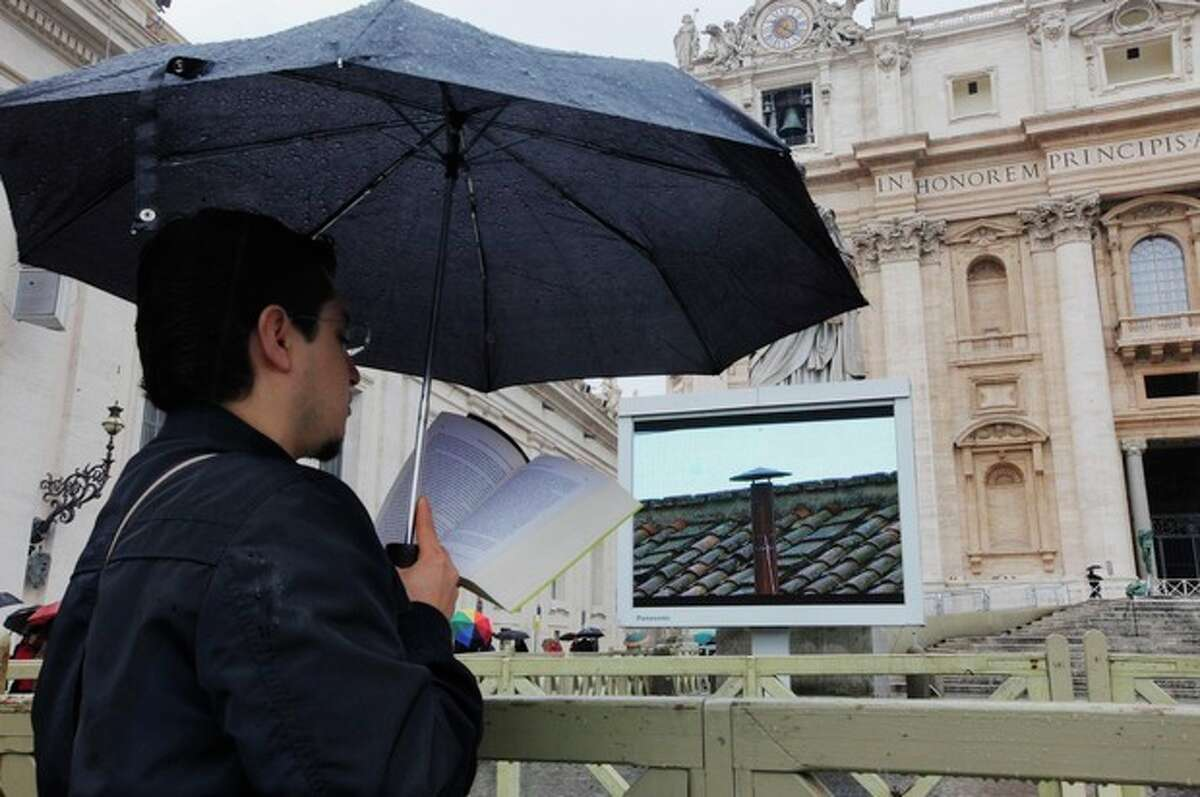 A visitor reads while waiting for smoke to emerge from the chimney on the Sistine Chapel during the second day of the conclave to elect a new pope in St. Peter's Square at the Vatican, Wednesday, March 13, 2013. (AP Photo/Dmitry Lovetsky)