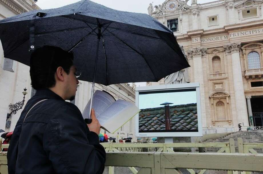 A visitor reads while waiting for smoke to emerge from the chimney on the Sistine Chapel during the second day of the conclave to elect a new pope in St. Peter's Square at the Vatican, Wednesday, March 13, 2013. (AP Photo/Dmitry Lovetsky) / AP