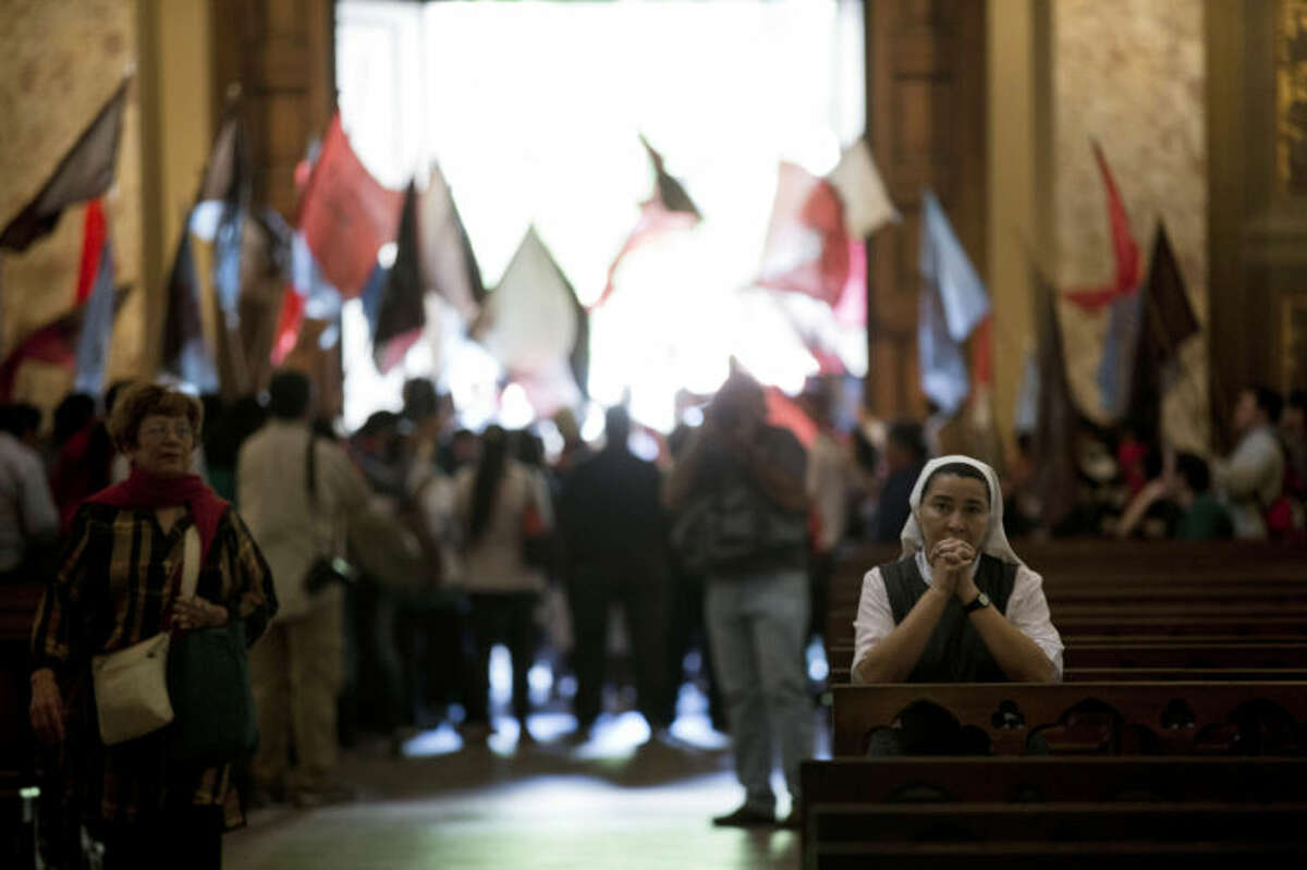 A Catholic nun prays as demonstrators protest government subsidies for Catholic education in the Metropolitan Cathedral in Buenos Aires, Argentina, Tuesday, March 12, 2013. Cardinals from around the globe locked themselves inside the Sistine Chapel on Tuesday to choose a new leader for the world's 1.2 billion Catholics and their troubled church. The archbishop of Buenos Aires, Cardinal Jorge Mario Bergoglio, 76, reportedly got the second-most votes after Joseph Ratzinger in the 2005 papal election, and he has long specialized in the kind of pastoral work that some say is an essential skill for the next pope. Demonstrators said government education subsidies for private education goes mostly to Catholic schools and demand more funding for public education. (AP Photo/Natacha Pisarenko)