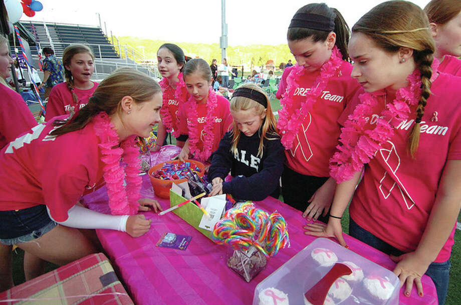 """Hour Photo/ Alex von Kleydorff. 7 yr old Molly Snow picks out her prizes from the bean bag toss with help from members of """"The Dream Team' who raised more than Ten Thousand dollars for Wiltons Relay for Life and The American Cancer Society. / 2012 The Hour Newspapers"""