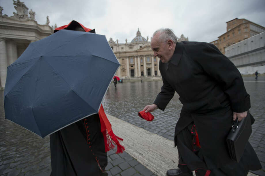 Argentine Cardinal Jorge Mario Bergoglio, right, picks up Canadian Cardinal Marc Ouellet's skull cap after the wind blew it off as they walk in St. Peter's Square after attending a cardinals' meeting, at the Vatican, Wednesday, March 6, 2013. Cardinals are meeting to discuss the problems of the church and to get to know one another because there is no clear front-runner in the election of the new pope. (AP Photo/Andrew Medichini)