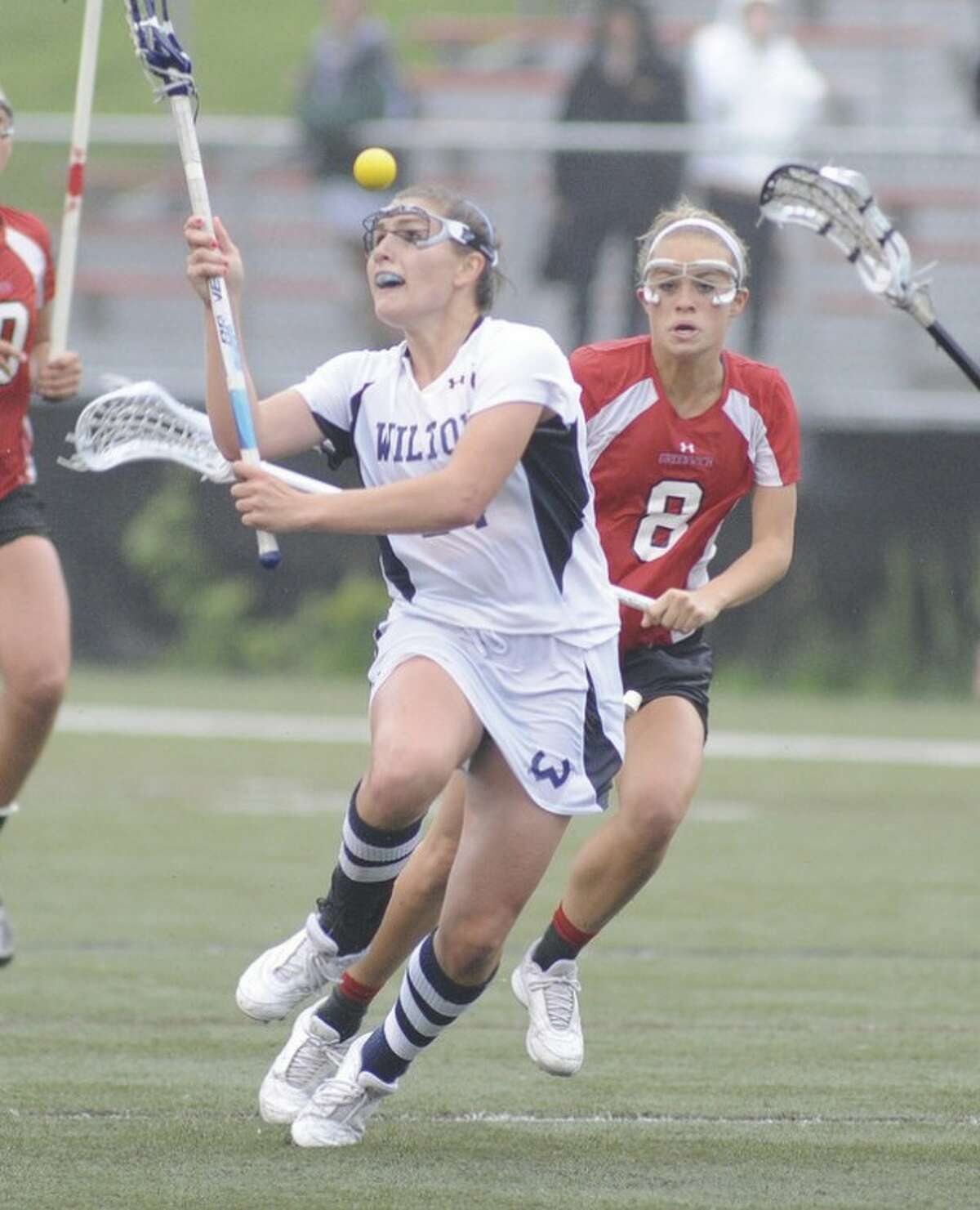 Hour photo/John Nash Wilton's Casey Pearsall, left, has the ball checked from her stick by Greenwich's Tori Dunster late in the second half of Monday's FCIAC girls lacrosse semifinal at Dunning Field. Greenwich held off the Warriors to take an 11-10 win.