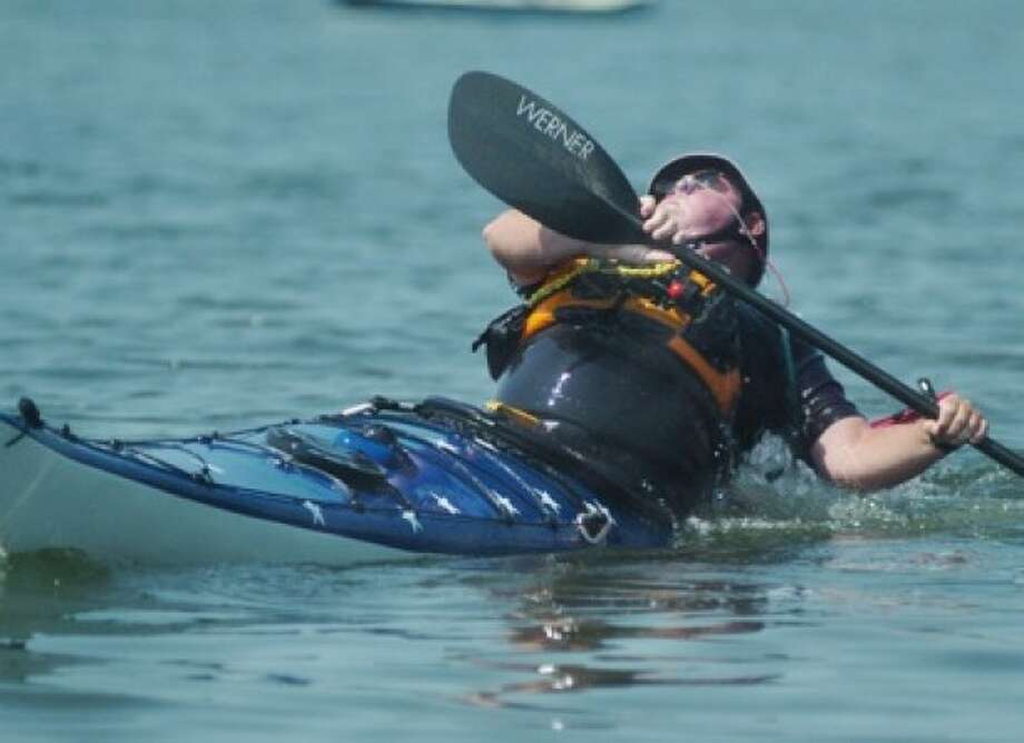 Kayak instructor Sheldon Penn assists the Outdoor Sports Center Sunday and demonstrates an Eskimo Roll in a kayak at the Norwalk Sailing School Sunday at Calf Pasture Beach. hour photo/matthew vinci