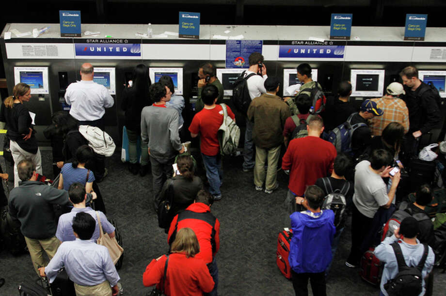 FILE - In this June 17, 2011, file photo, passengers crowd the kiosks to check in and print boarding passes at San Francisco International Airport in San Francisco. Airlines are setting aside more rows for passengers willing to pay extra for a better seat. That means families are going to struggle to sit next to each other unless they booked early or are willing to shell out anywhere from $5 to $180 extra, each way. (AP Photo/George Nikitin, File) / AP2011