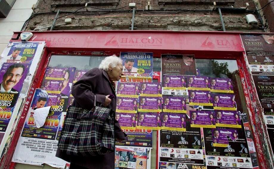 A woman walks past a closed-down travel agency plastered with concert posters in Madrid Monday May 21, 2012. Spain's economy minister de Guindos said the Spanish economy, which has contracted by 0.3 percent in each of the past two quarters, will shrink by about the same amount in the second quarter of 2012. The forecast is for it to decline 1.7 percent for the year. Unemployment stands at a staggering 24.4 percent, and exceeds 50 percent for people under age 25.(AP Photo/Paul White) / AP